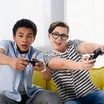 multicultural teen boys playing video game at home