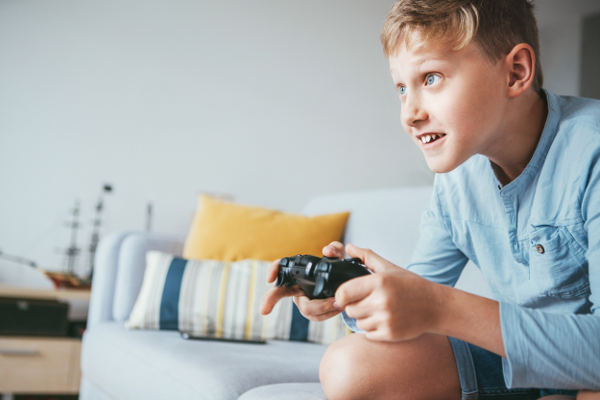Teenager boy enthusiastically plays the game console