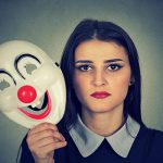 Young woman with sad face expression holding clown mask expressing cheerfulness happiness isolated on gray wall background
