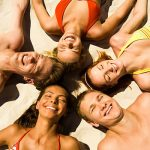 Image of happy five teens lying on the sand