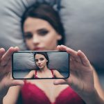 Top above high angle view portrait of nice trendy attractive exquisite charming girl lying on linen sheets in lace maroon red bra taking selfie on smart gadget device posing teasing waiting husband