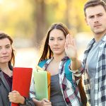 Three angry students gesturing stop in a park